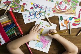 Closeup of child coloring holiday drawings with pencils