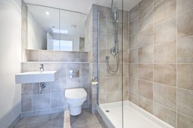 Modern en suite bathroom with large shower, toilet and wash basin in beige natural with natural stone tiled walls.