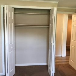 Bedroom with closet and door to living area - Kent's Best Apartments