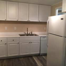 Kitchen with white cabinets, sink, and fridge - Kent's Best Apartments