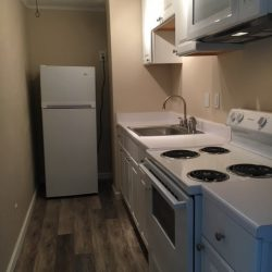 Galley kitchen with white cabinets and appliances at Kent's Best Apartments