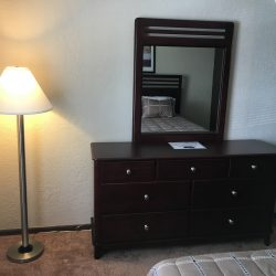 Bedroom with dresser and lamp - Kent's Best Apartments