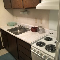 Kitchen area with sink, stove, and cabinets - Kent's Best Apartments