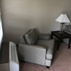 Living room with air conditioner and couches - Kent's Best Apartments