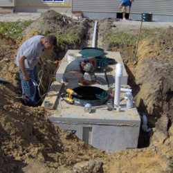Far shot of man attending to septic system