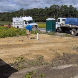 Far shot of man near septic pump with vehicles nearby