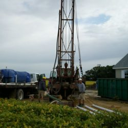 Image of well drill and loading truck near a small building