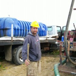 Image of smiling worker near water truck
