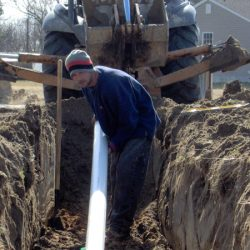 Image of man in trench holding PVC piping