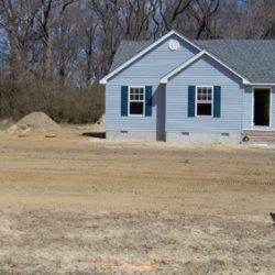 Home with completed septic installation in the foreground