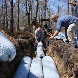 Image of employees placing additional absorption products in trench
