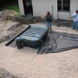 Image of septic tank and workers outside of house