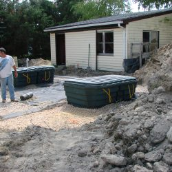 Far shot of uninstalled septic tank outside of house