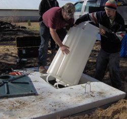 Image of employee installing septic parts