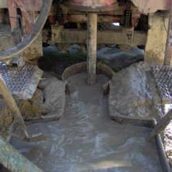 Image of well with workers shoveling around it