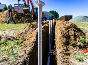 Image of PVC piping rising from trench