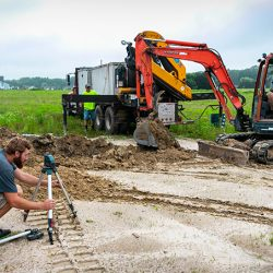Image of heavy machinery and a worker completing a project