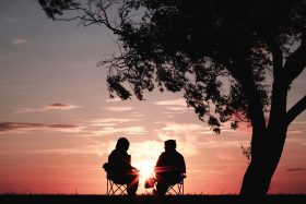 An image of two adults sitting under a tree watching the sunset.