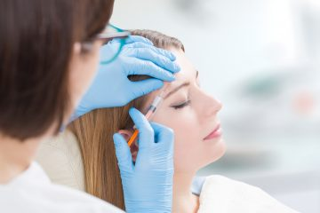 Woman getting facial dermal filers injected into her forehead