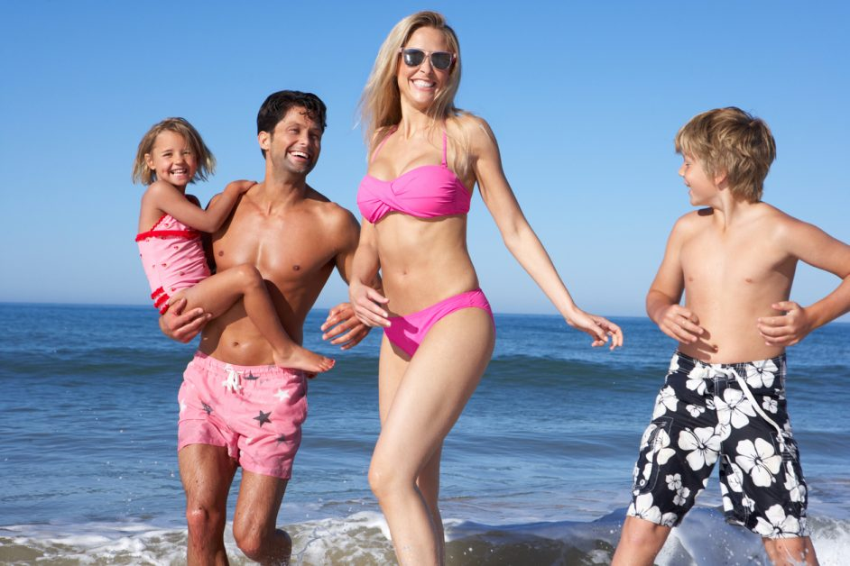 Mom in the ocean with her family after mommy makeover