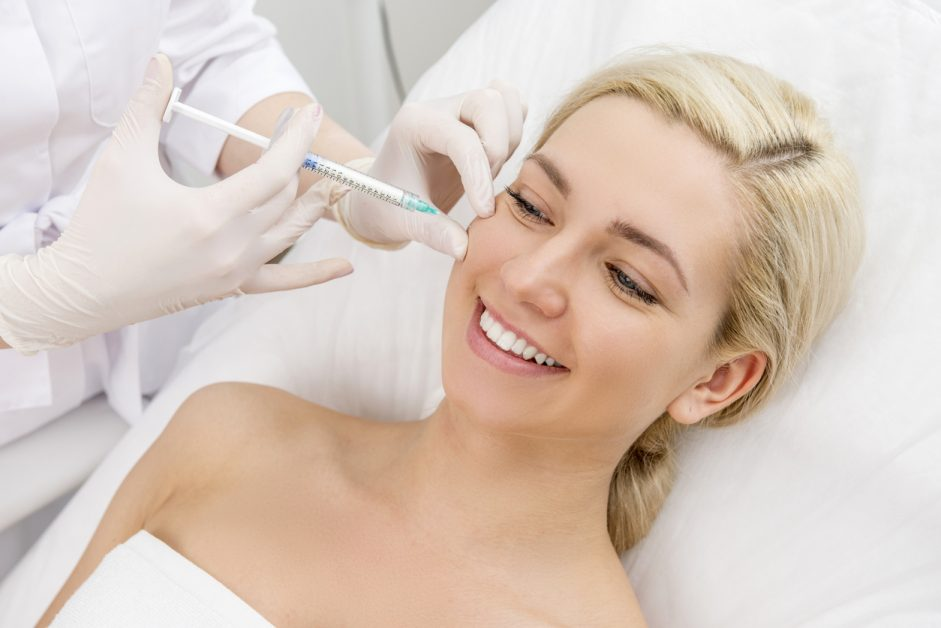 Woman smiling while getting a beauty facial injection