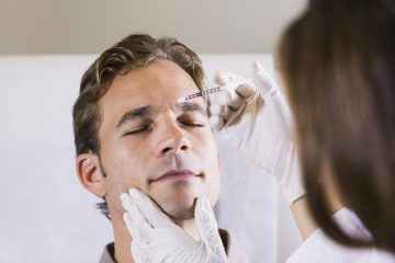 Mid adult man (30s) receiving botulinum toxin injection. Cosmetic Surgeries Done on Men concept