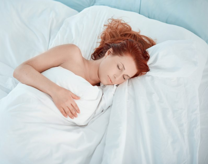 Beautiful woman resting her bed sleeping.red hair, eyes closed.photo taken inside bedroom. post-surgery