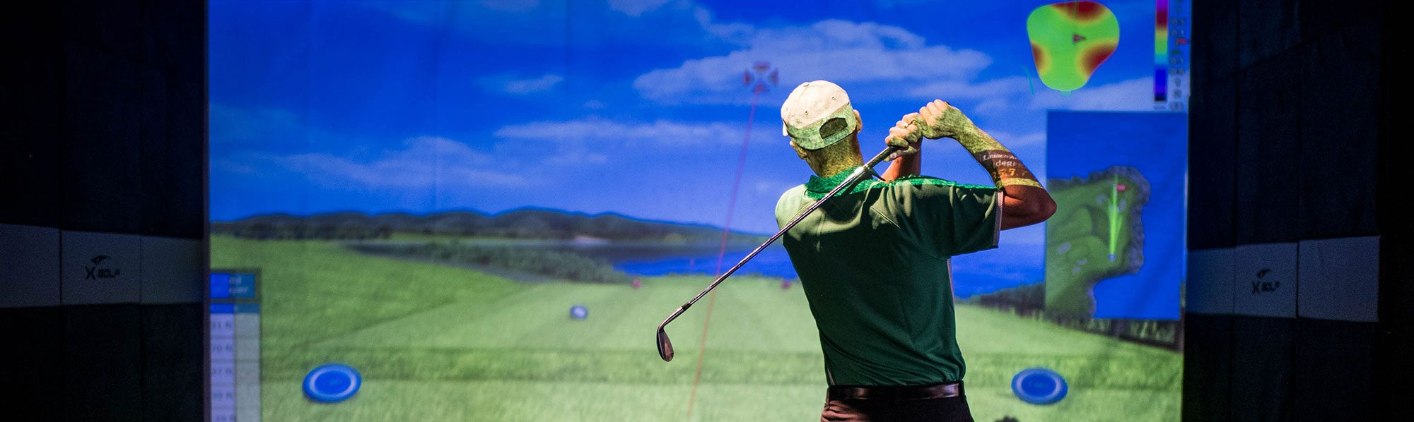 Image of man watching his golf shot in simulator bay