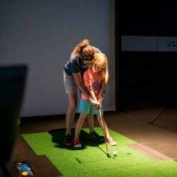 Young golfer taking a golf lesson at XGolf Fort Collins.