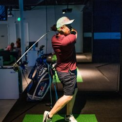 Golfer in his backswing at our golf simulator at XGolf Fort Collins.