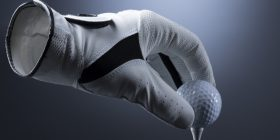 Image of glove teeing up golf ball
