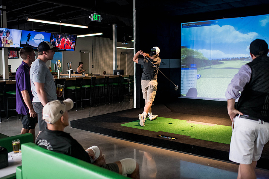 Golfer playing a round of virtual golf at XGolf Fort Collins.