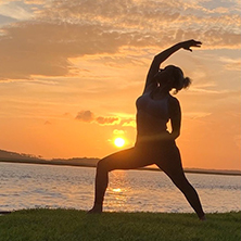 Image of a woman doing yoga at sunset
