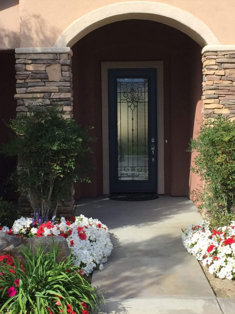Custom Veranda glass door behind flower lined walkway