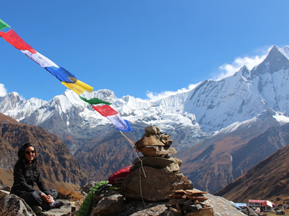 Student with prayer flags at the summit of Himalayan trek