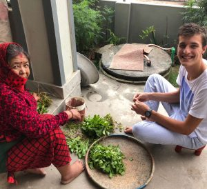 Student helps his host mom prepare a meal
