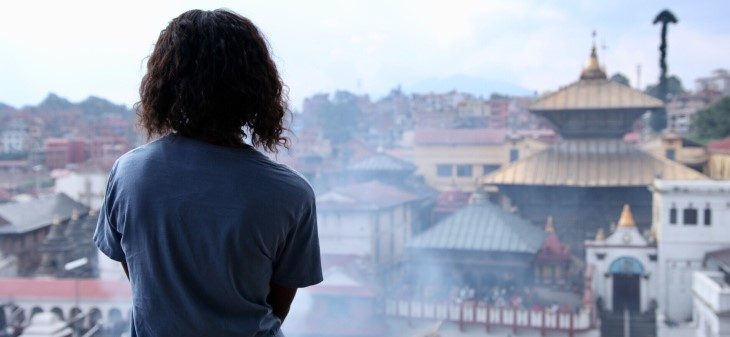 Student gazes at a view over a Buddhist temple