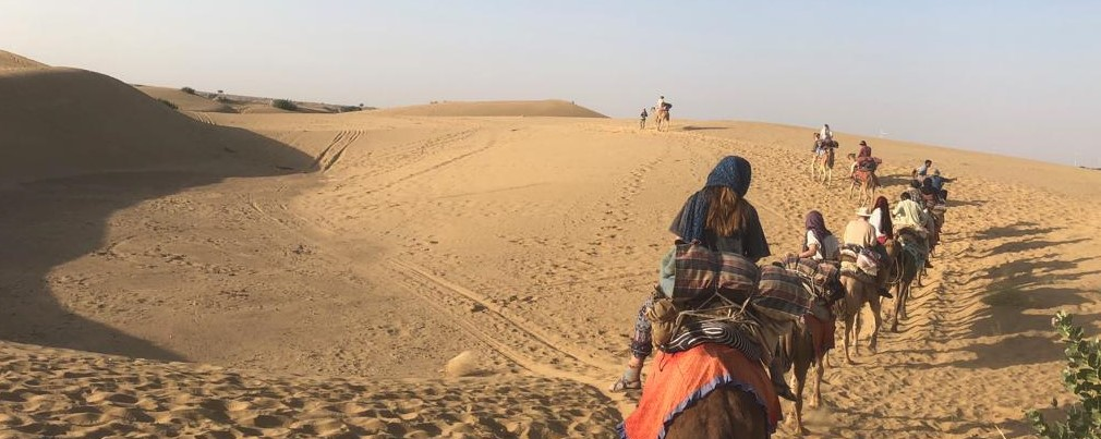 Group riding on camels through the desert