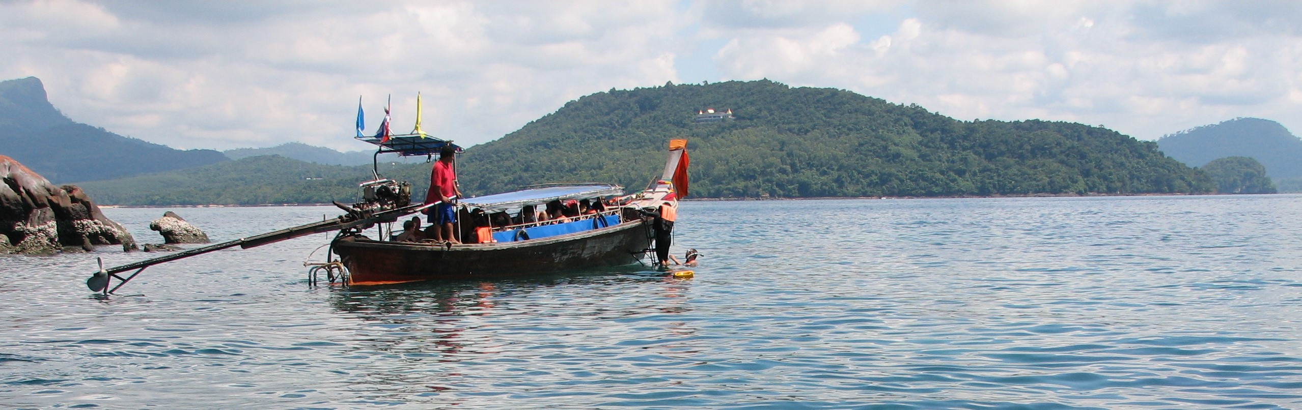 Group snorkels off a traditional boat in southern Thailand